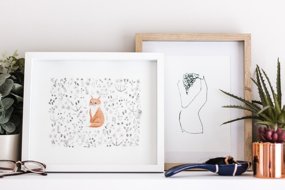 shallow focus photo of orange cat painting with white wooden frame