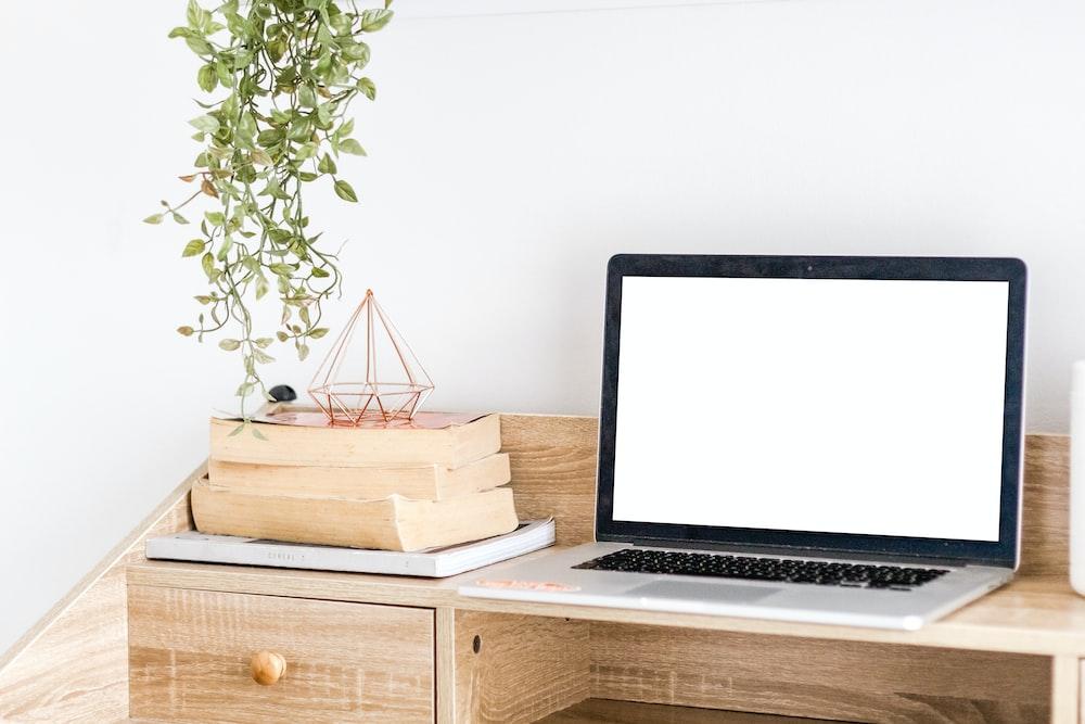 silver MacBook on wooden desk by wall