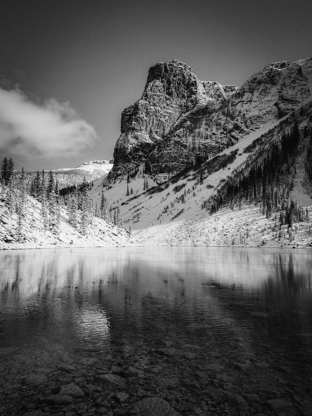 grayscale photography of calm body of water by mountains
