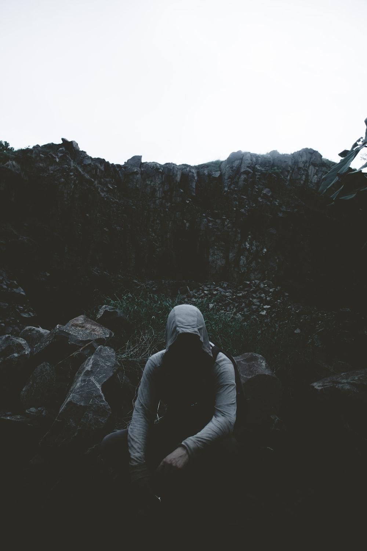 man wearing hoodie while sitting on ground