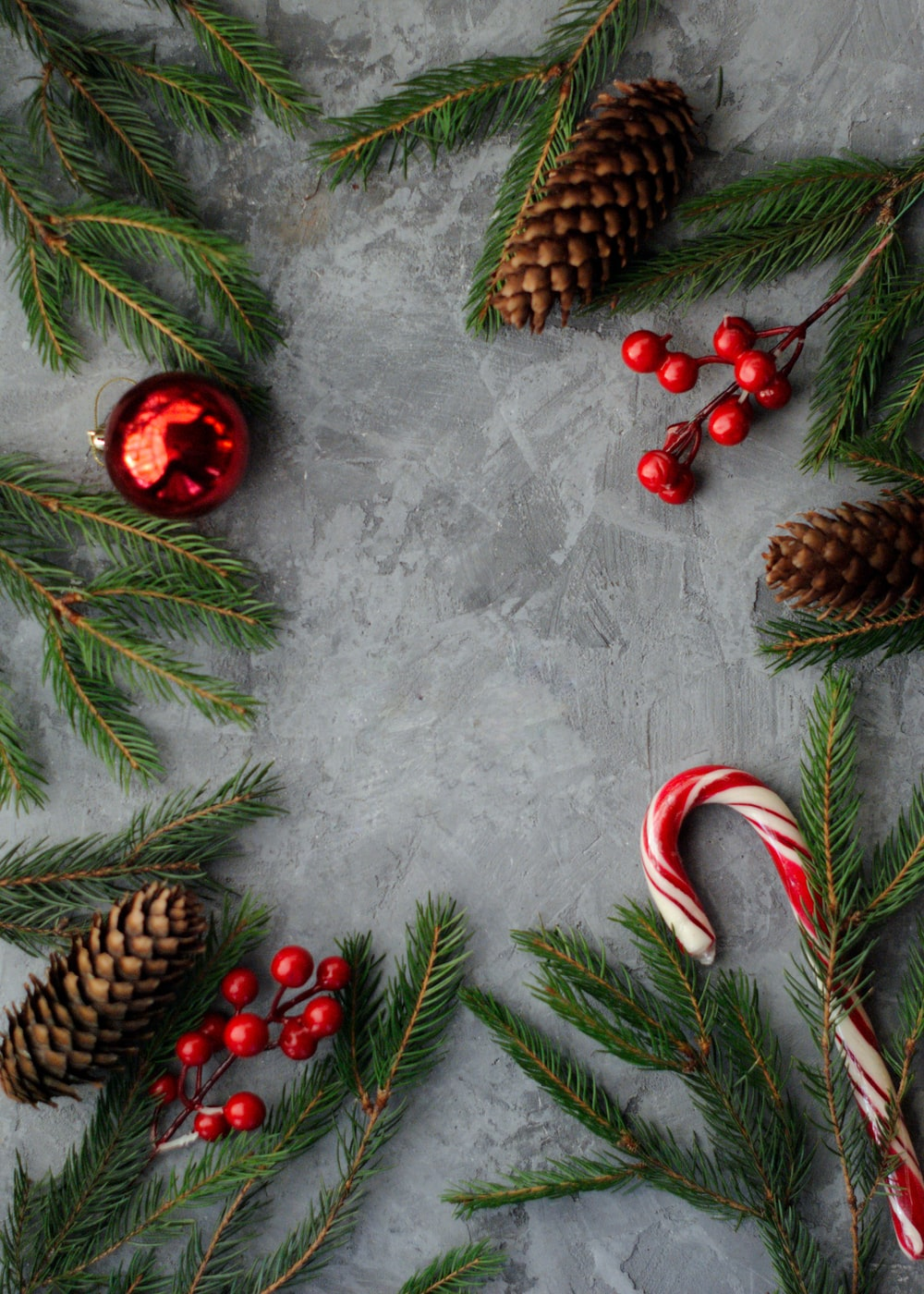 flat lay photography of pine cones, candy cane, green spruces, and mistletoes