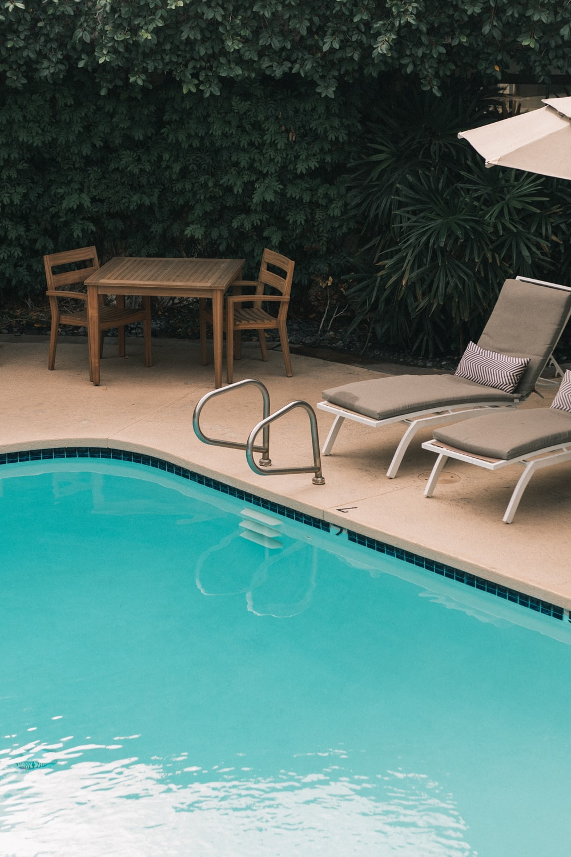 two gray sunbathing loungers beside pool