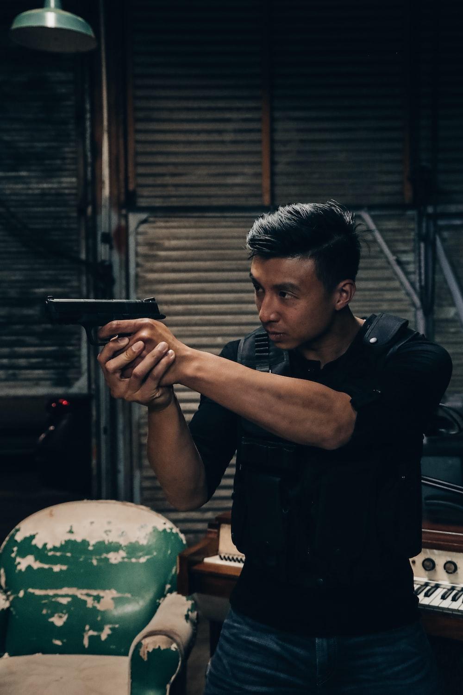 man holding pistol wearing black bulletproof vest