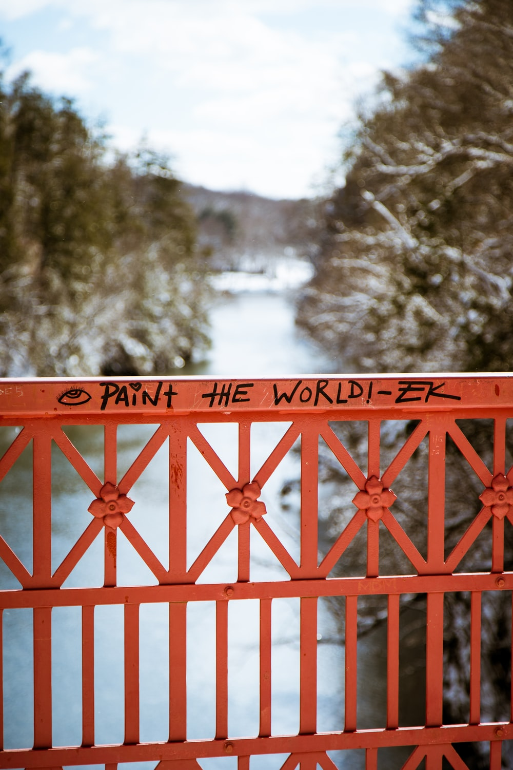 paint the world written on red metal bridge rail