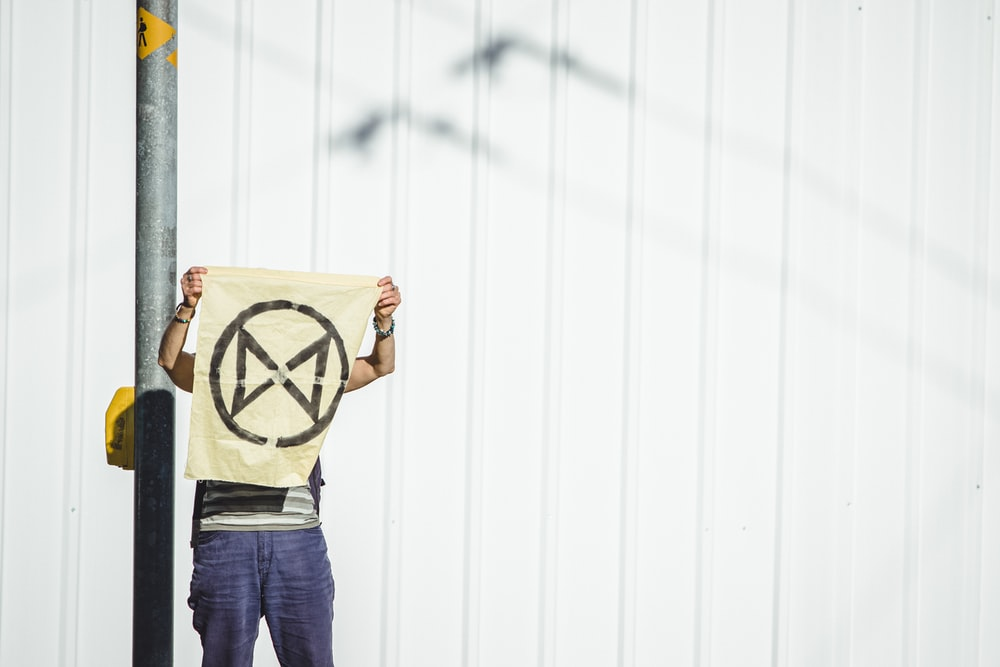 man holding banner standing beside metal post
