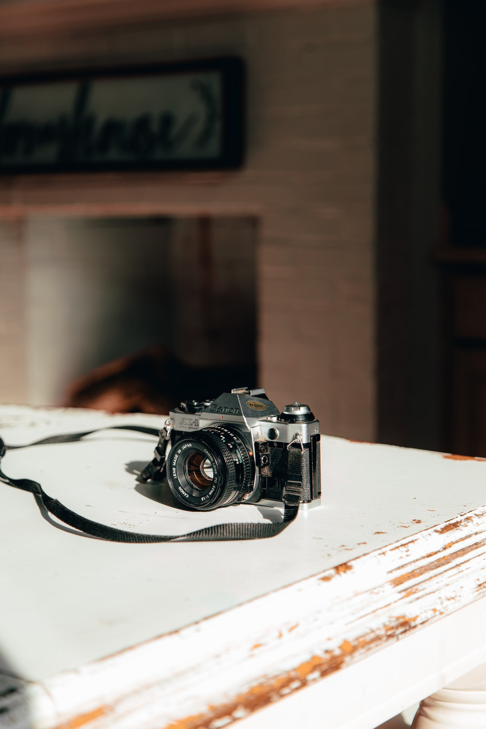 shallow focus photo of black SLR camera on white wooden table