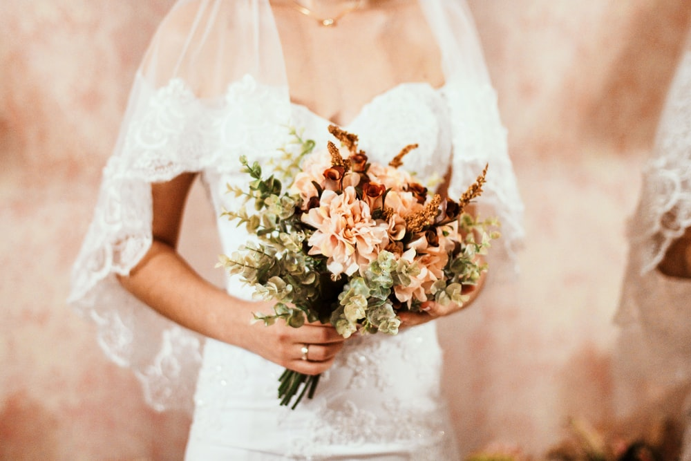 woman in white wedding dress holding bouquet of flower
