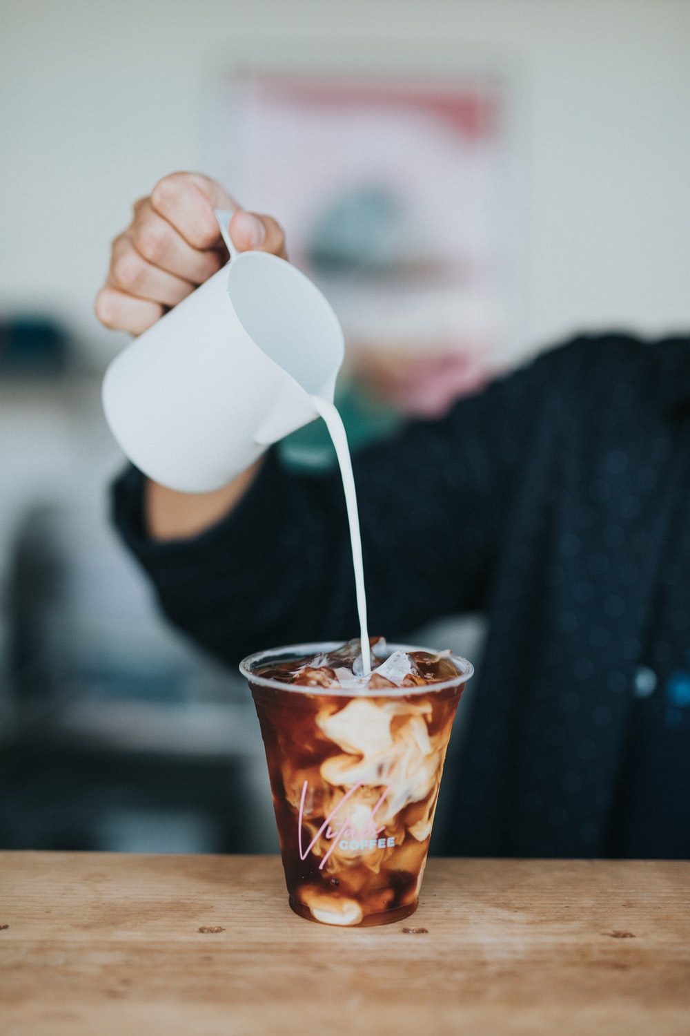 person pouring cream on cup