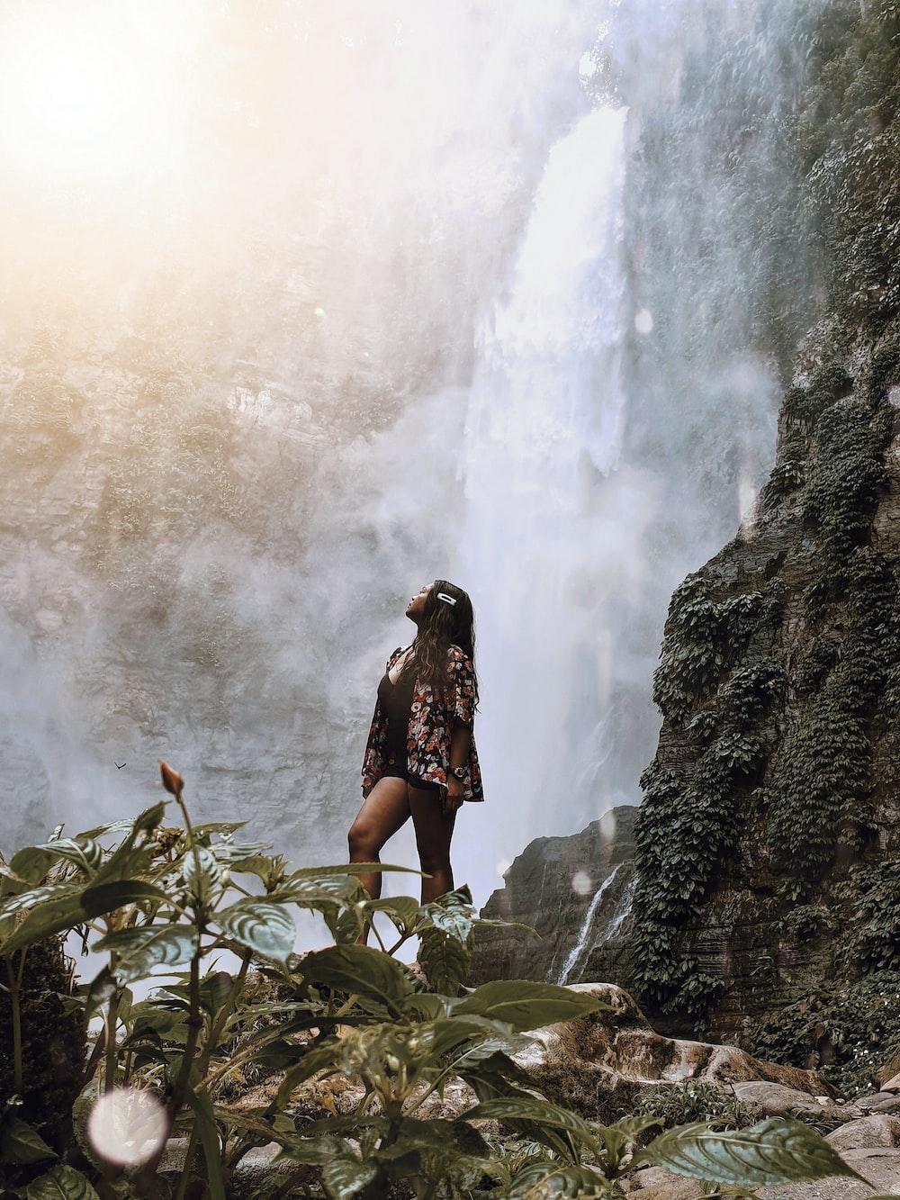 woman looking up at waterfalls
