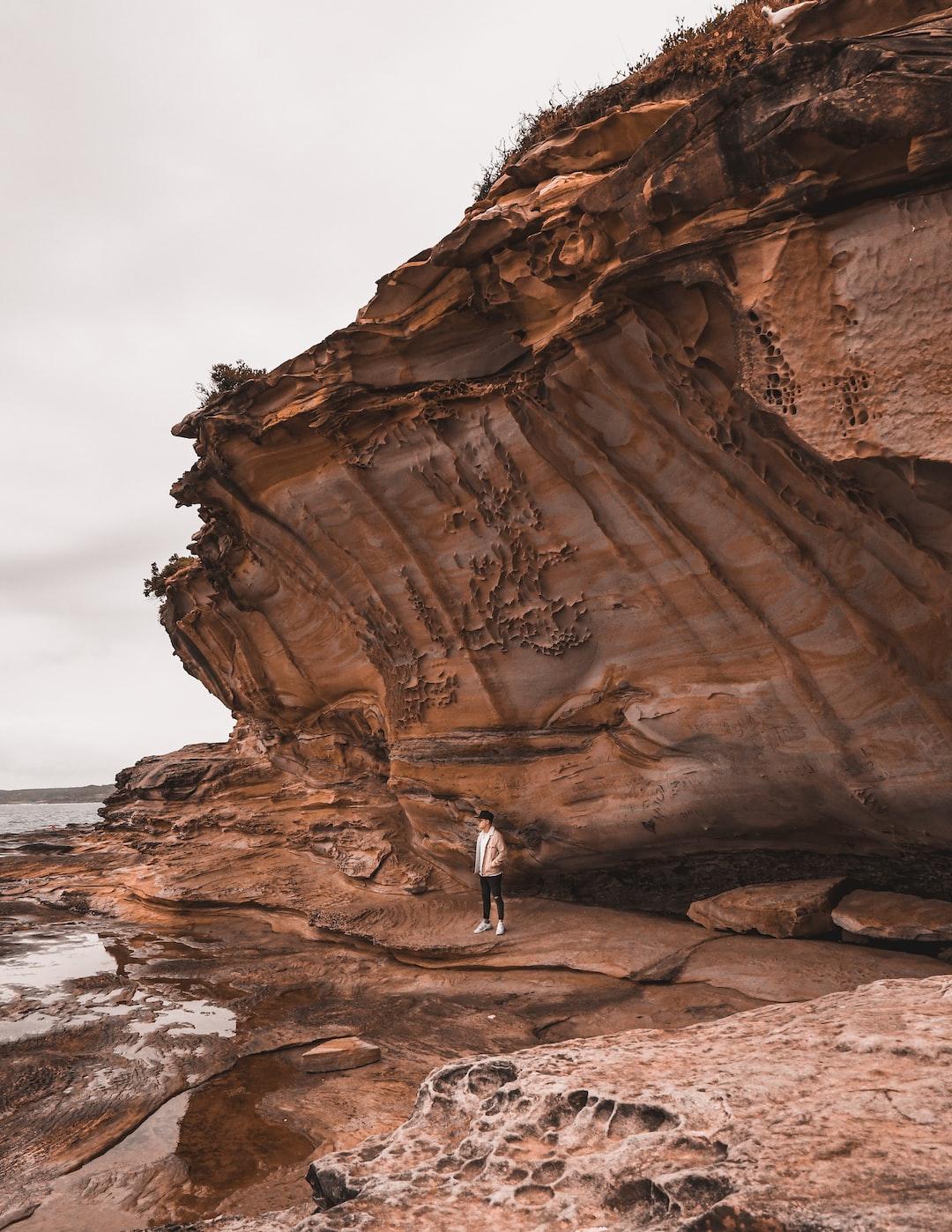 Man standing under sandstone cliffs on Bare Island, Australia.