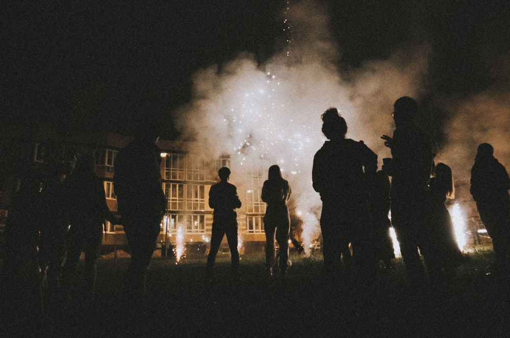 silhouette photography of people standing near smoke and building during nighttime