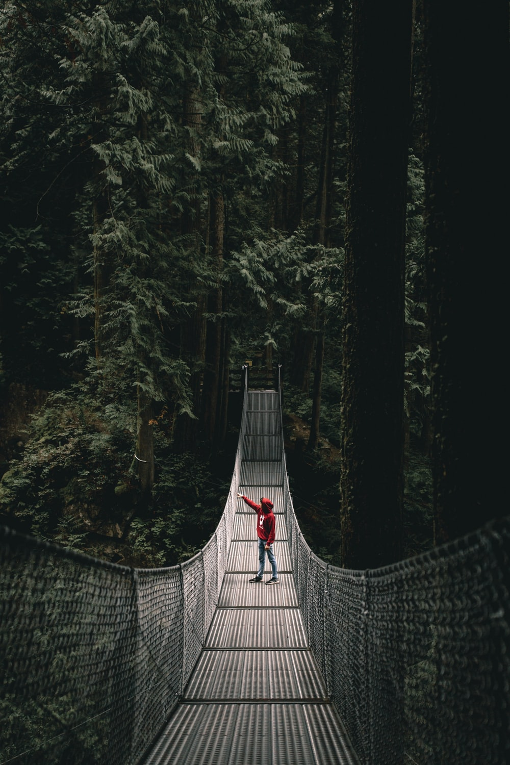 person wearing red hoodie standing on the hanging bridge