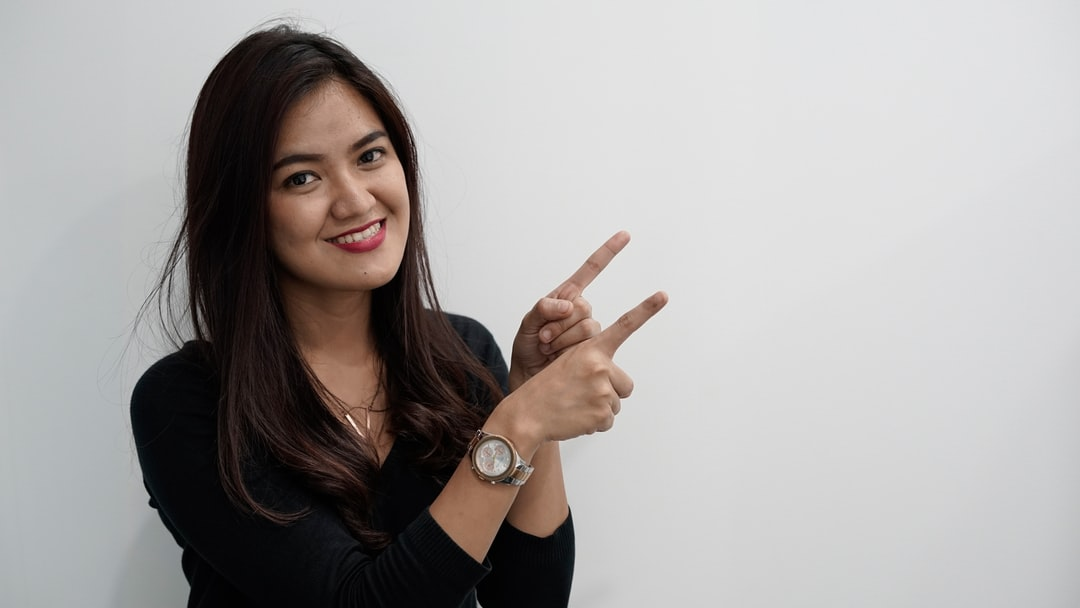 Asian woman pointing at side