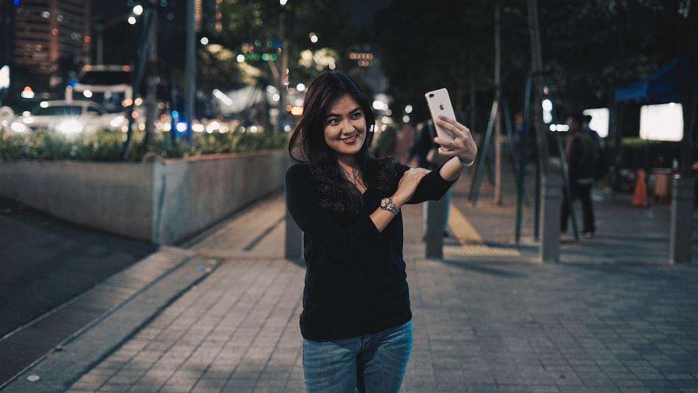 woman taking selfie near outdoor during nighttime