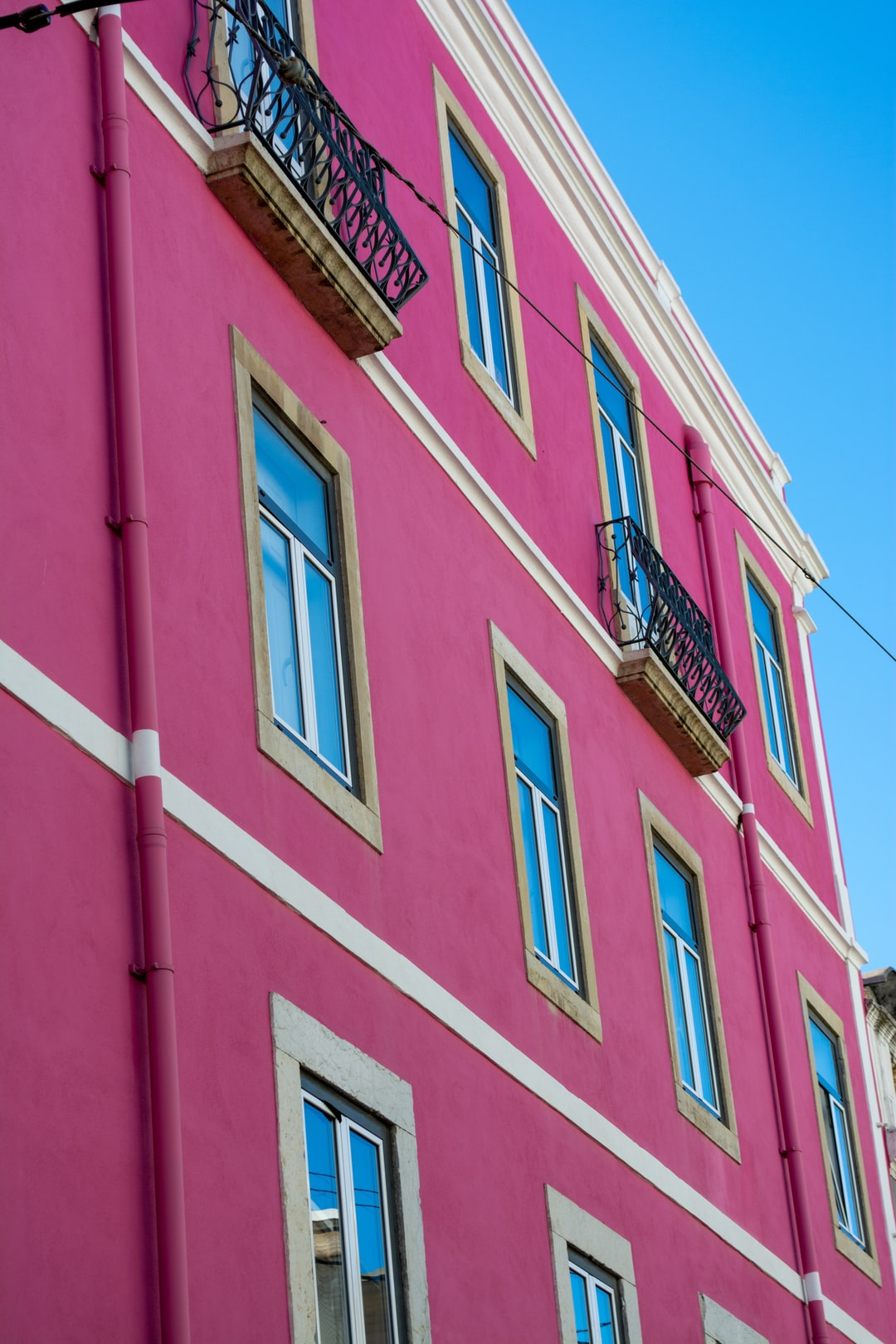 A pink house rising into the blue sky