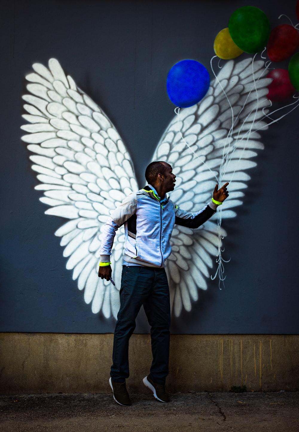 man standing in front of white wings and assorted-color balloons graffiti on wall