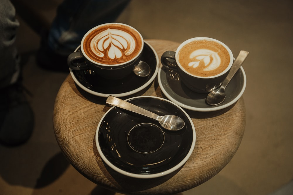 two cups of latte on round brown stool