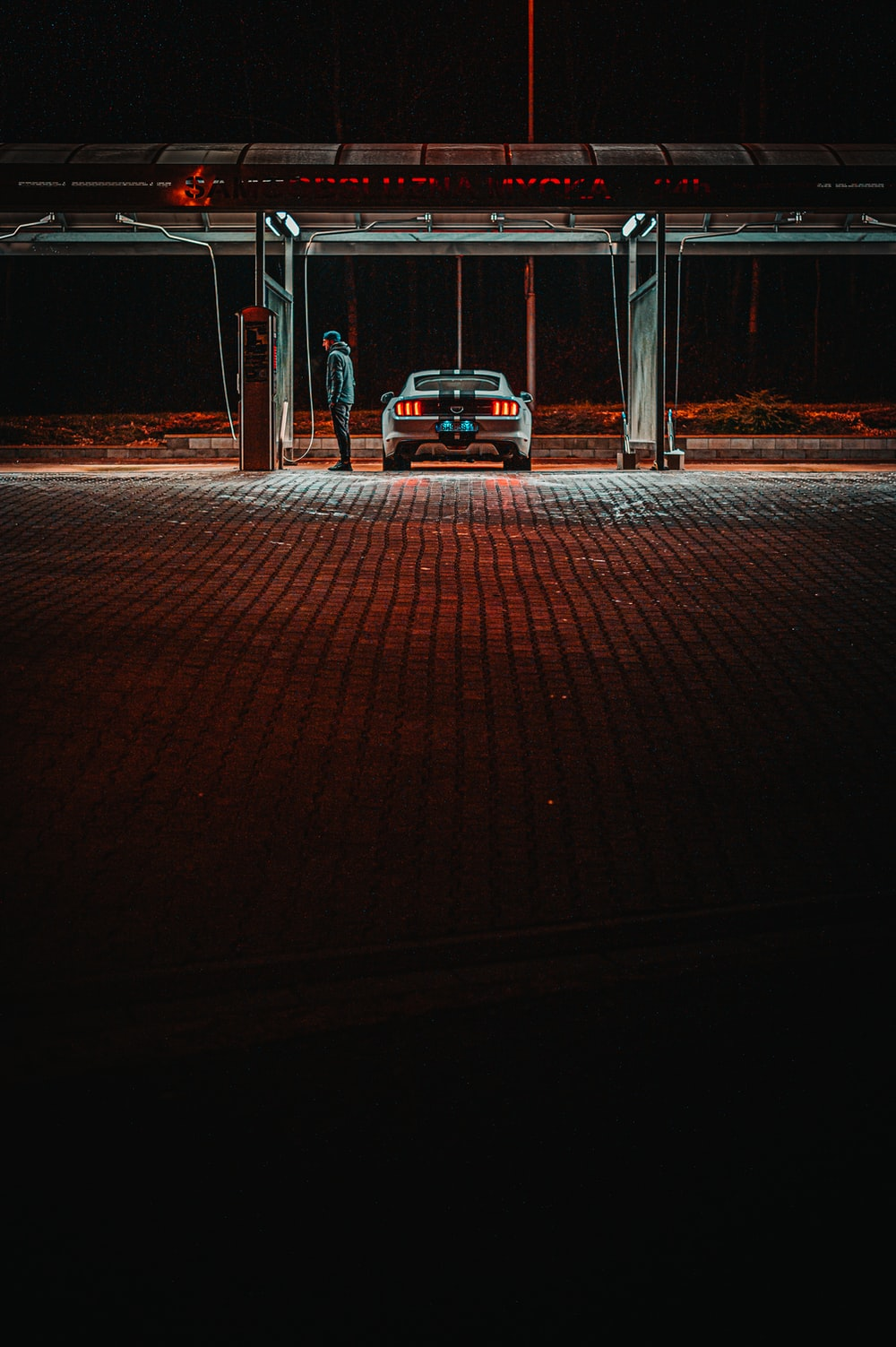 man standing near gasoline station beside vehicle during night time