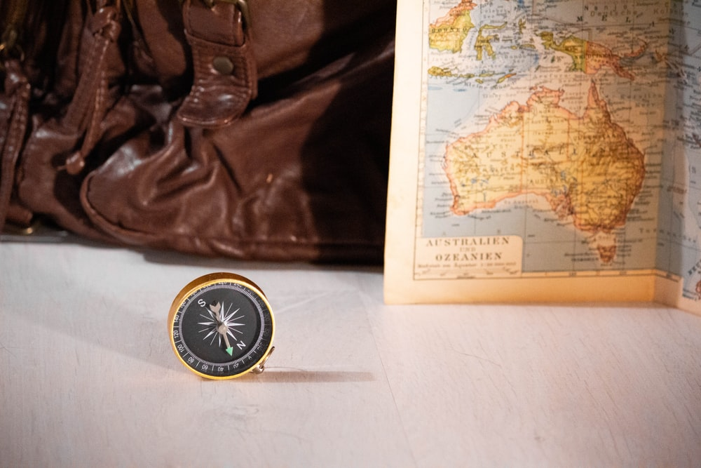 gold and black compass near map chart