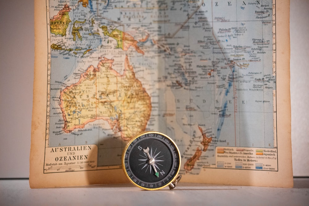 round gold and black compass and map chart