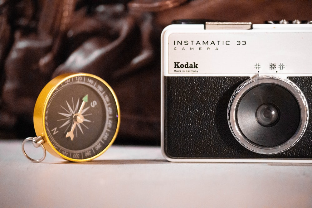 black and white Kodak Instamatic 33 camera and round black and gold compass