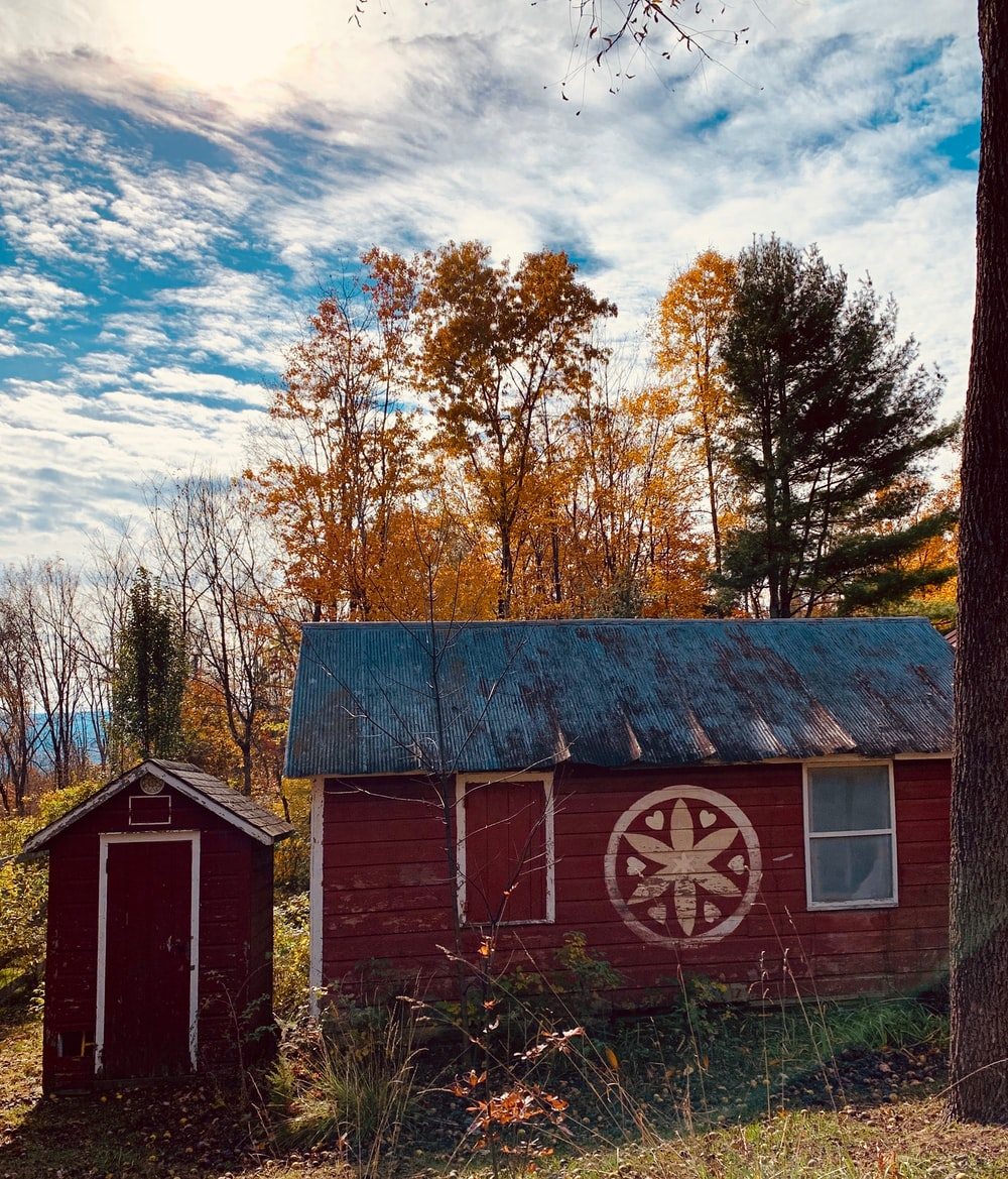 red wooden house and shed near trees under blue cloudy sky