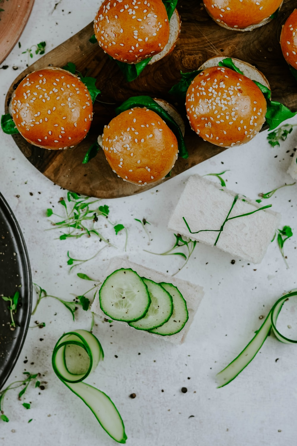 burgers on wooden surface near cucumber slices