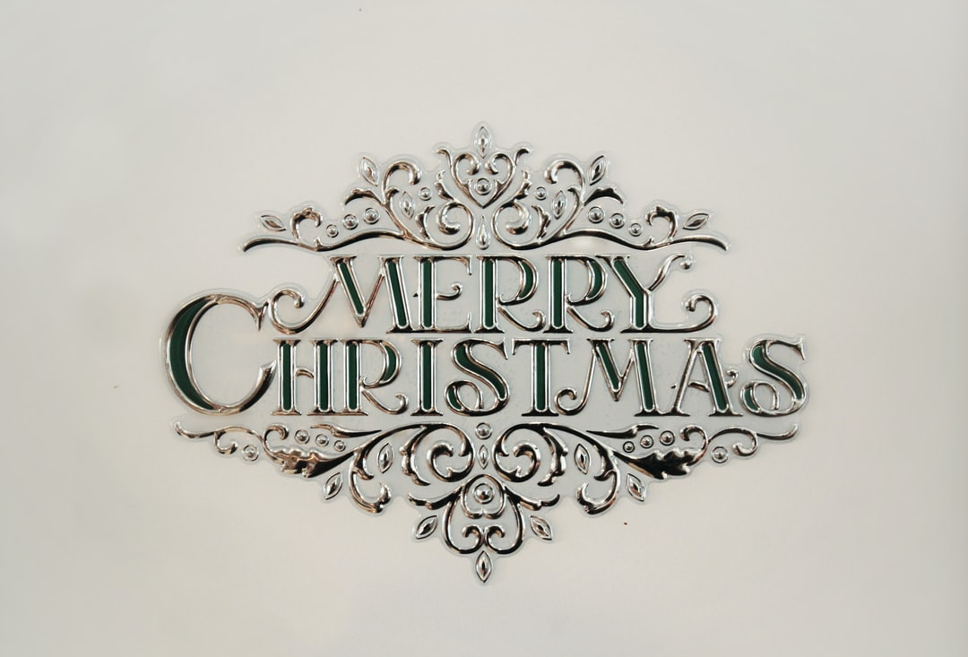 A Merry Christmas sign against a white wall.