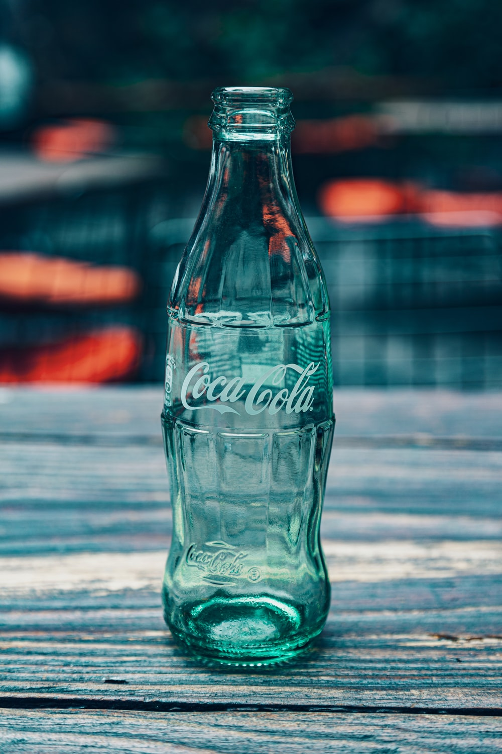 Coca-Cola glass bottle on wooden surface