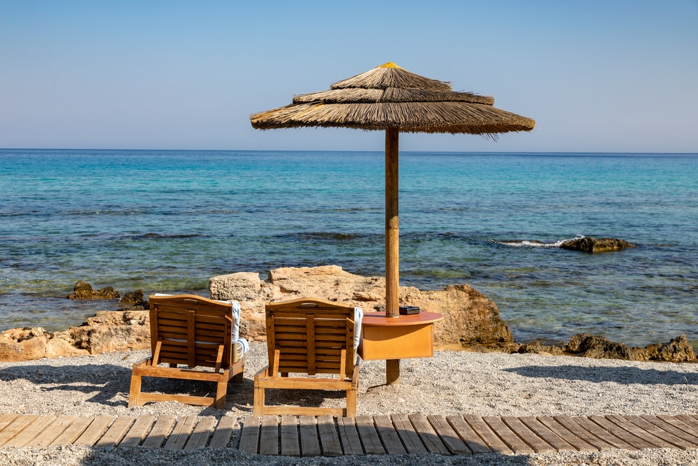 brown lounge chairs beside parasol on island during day