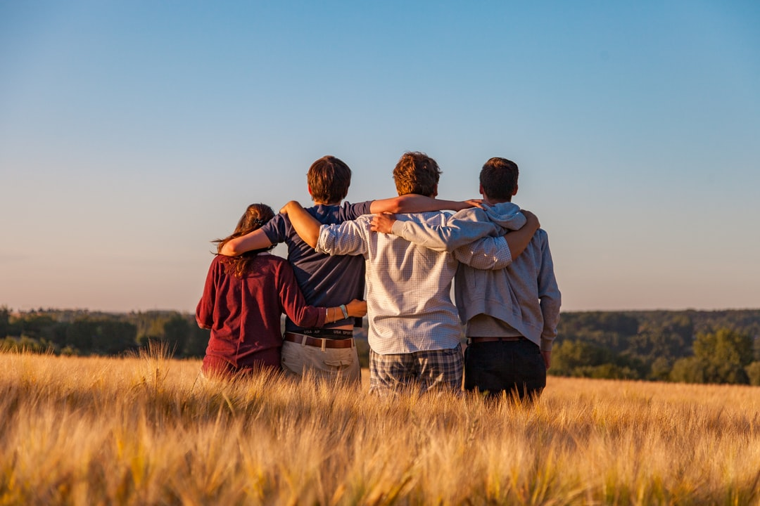 Four people enjoying a group hug in a field.