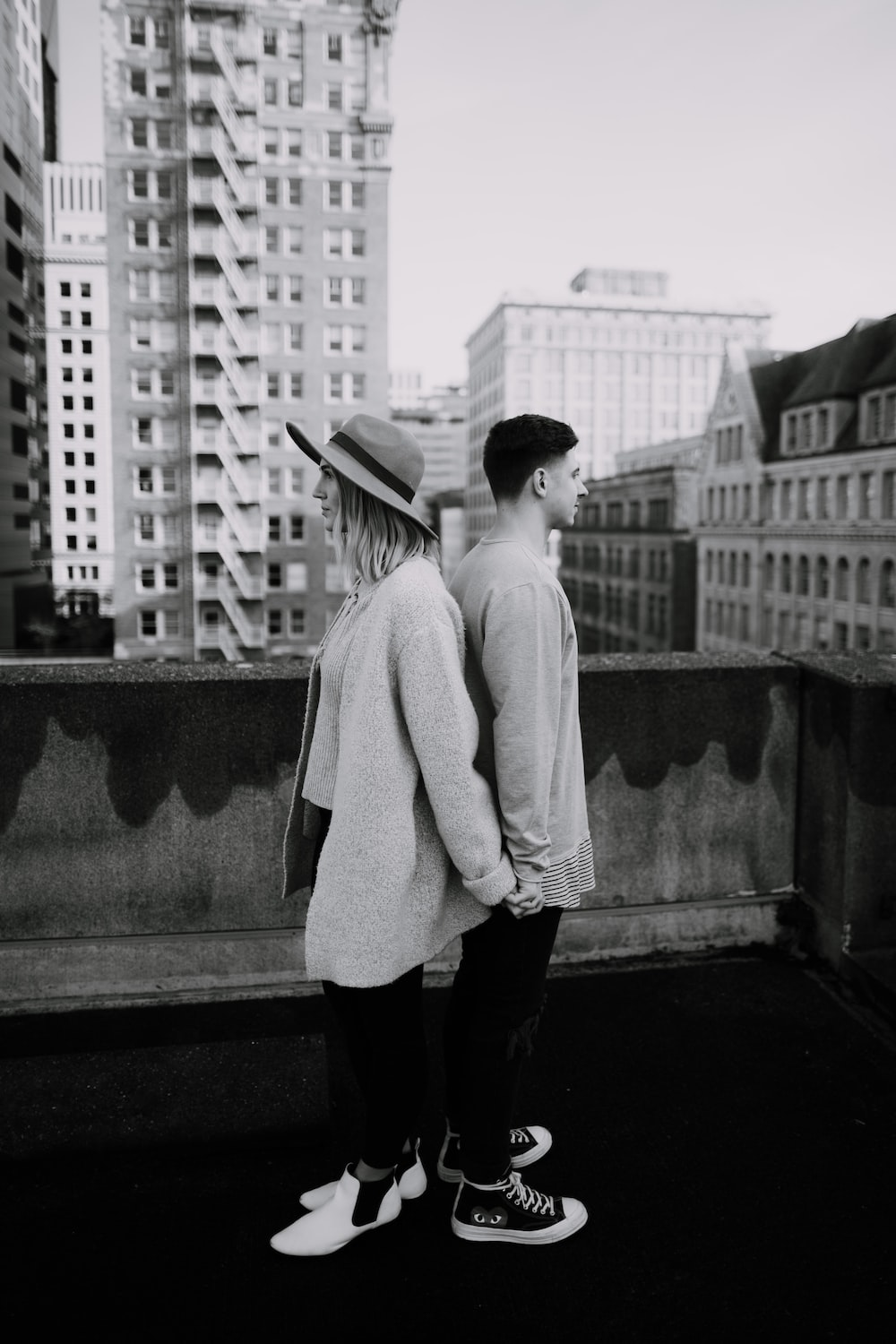 grayscale photography of standing man and woman near outdoor during daytime