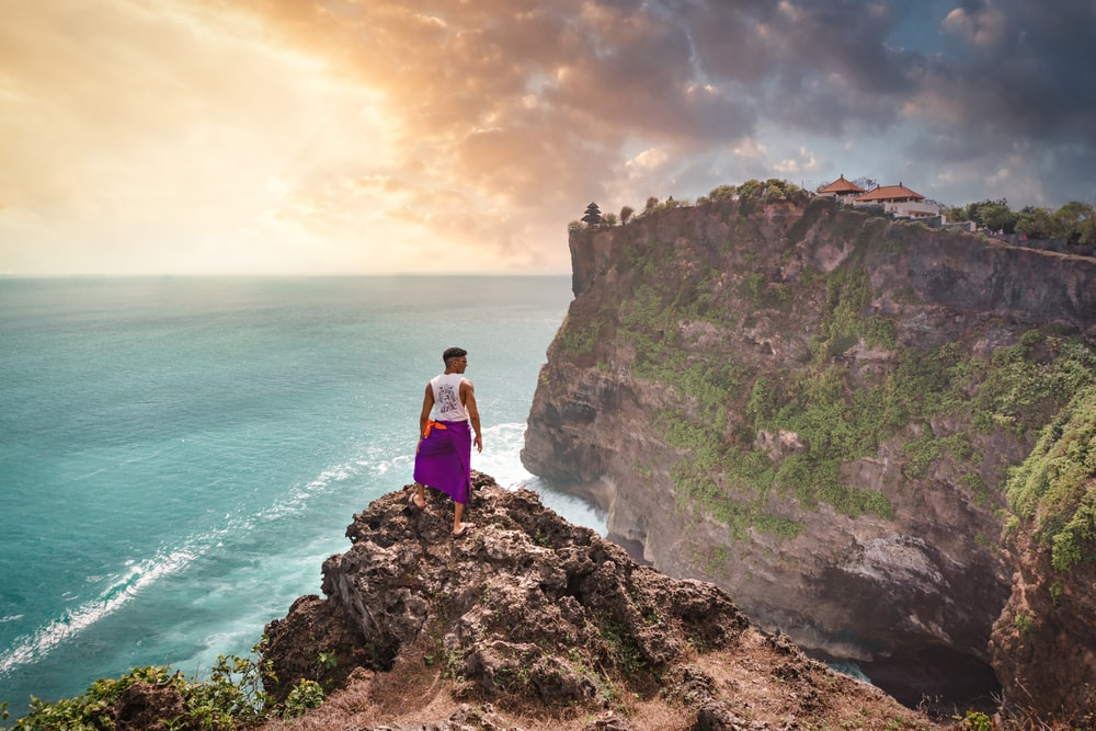 person standing on cliff in front of ocean during daytime