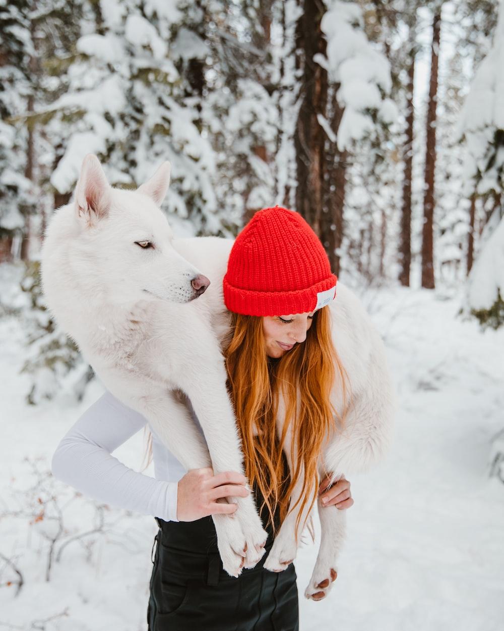 woman lifting white dog