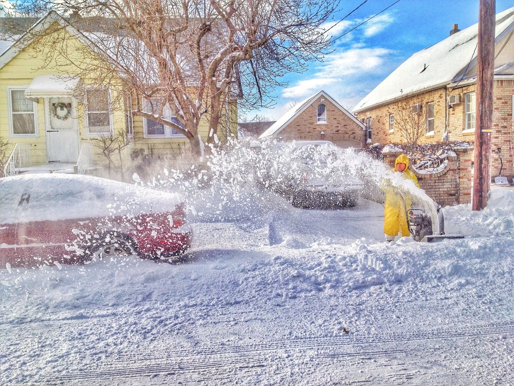 man using snow thrower