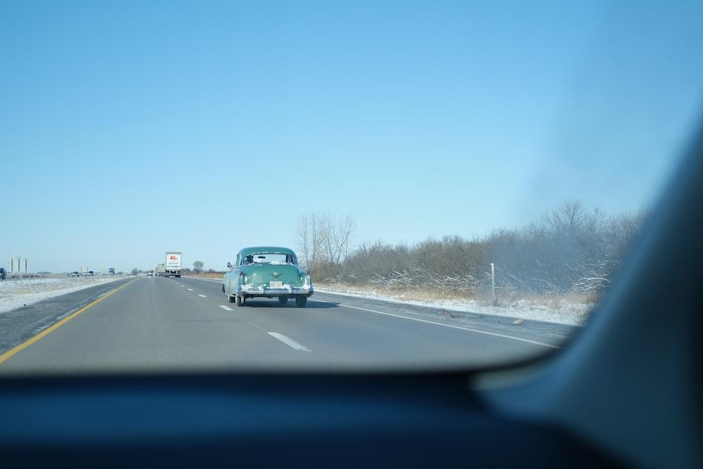 teal vehicle on road
