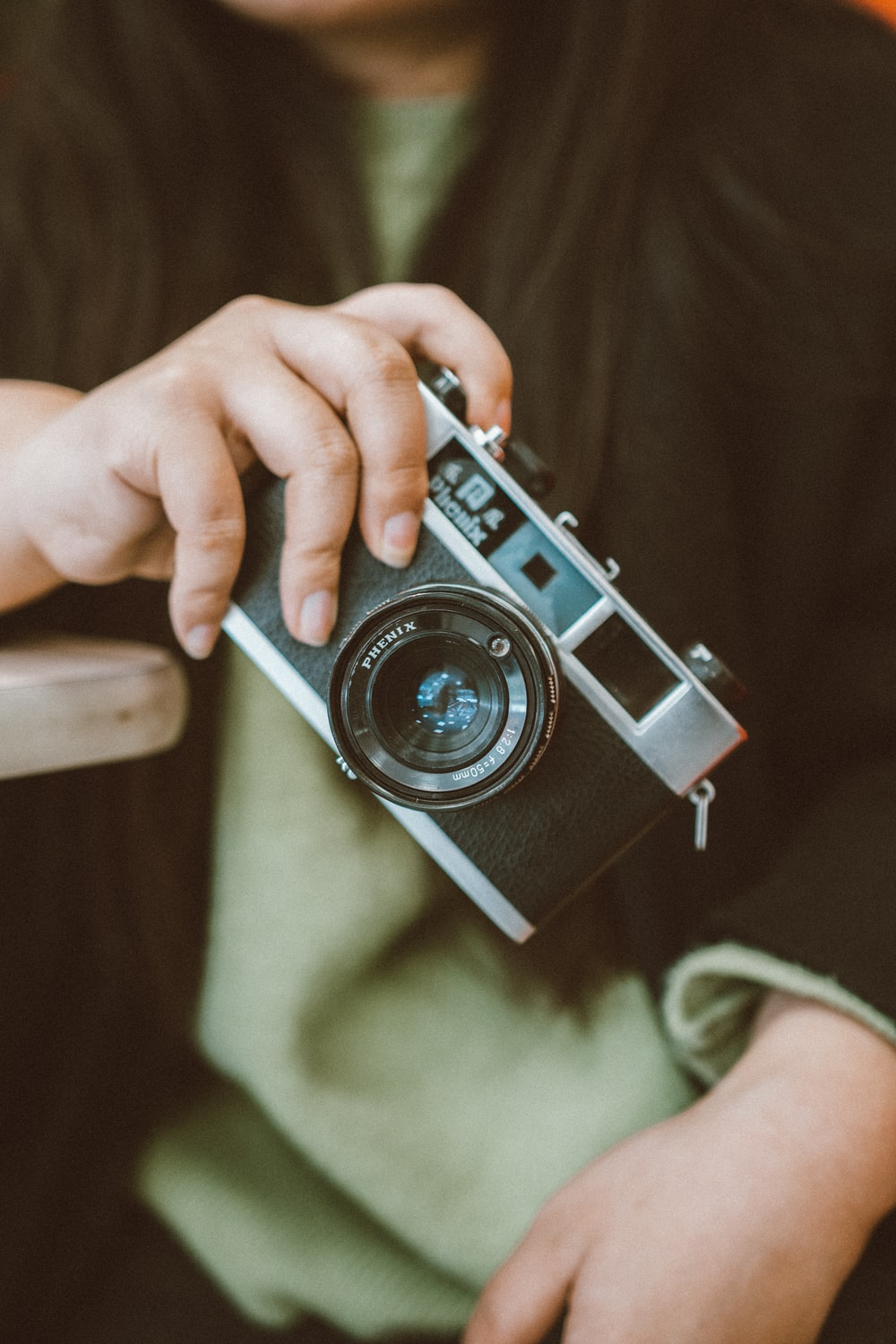 person holding black and gray DSLR camera