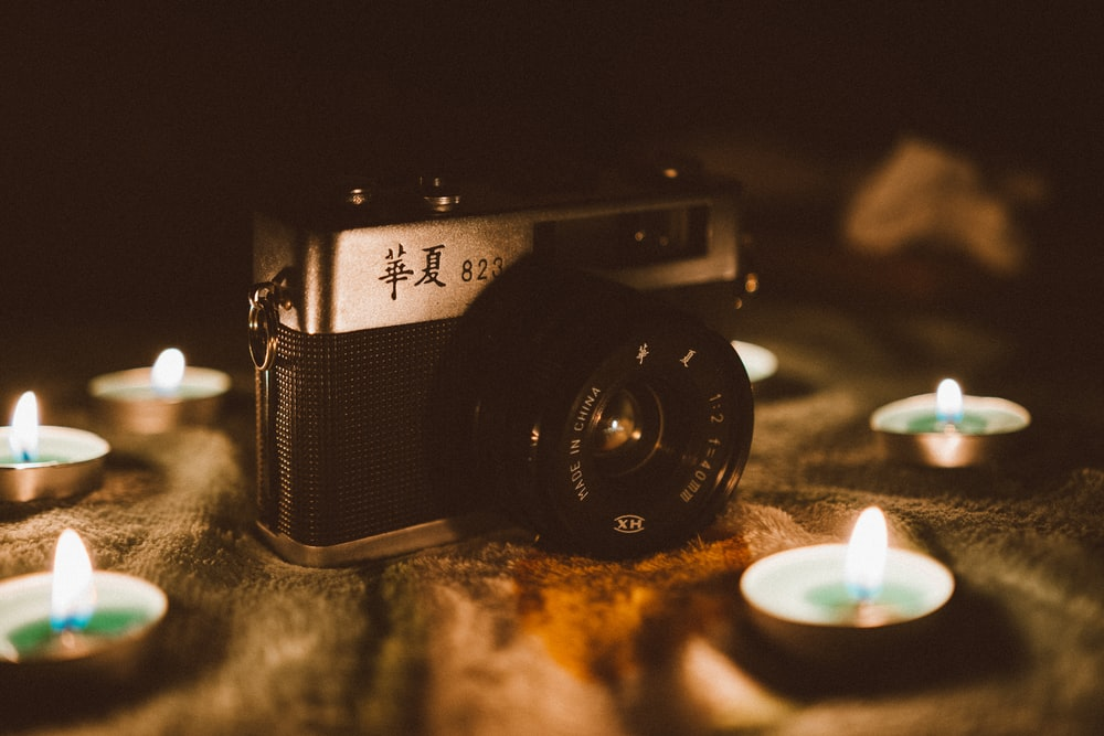 black and silver DSLR camera between tealight candles
