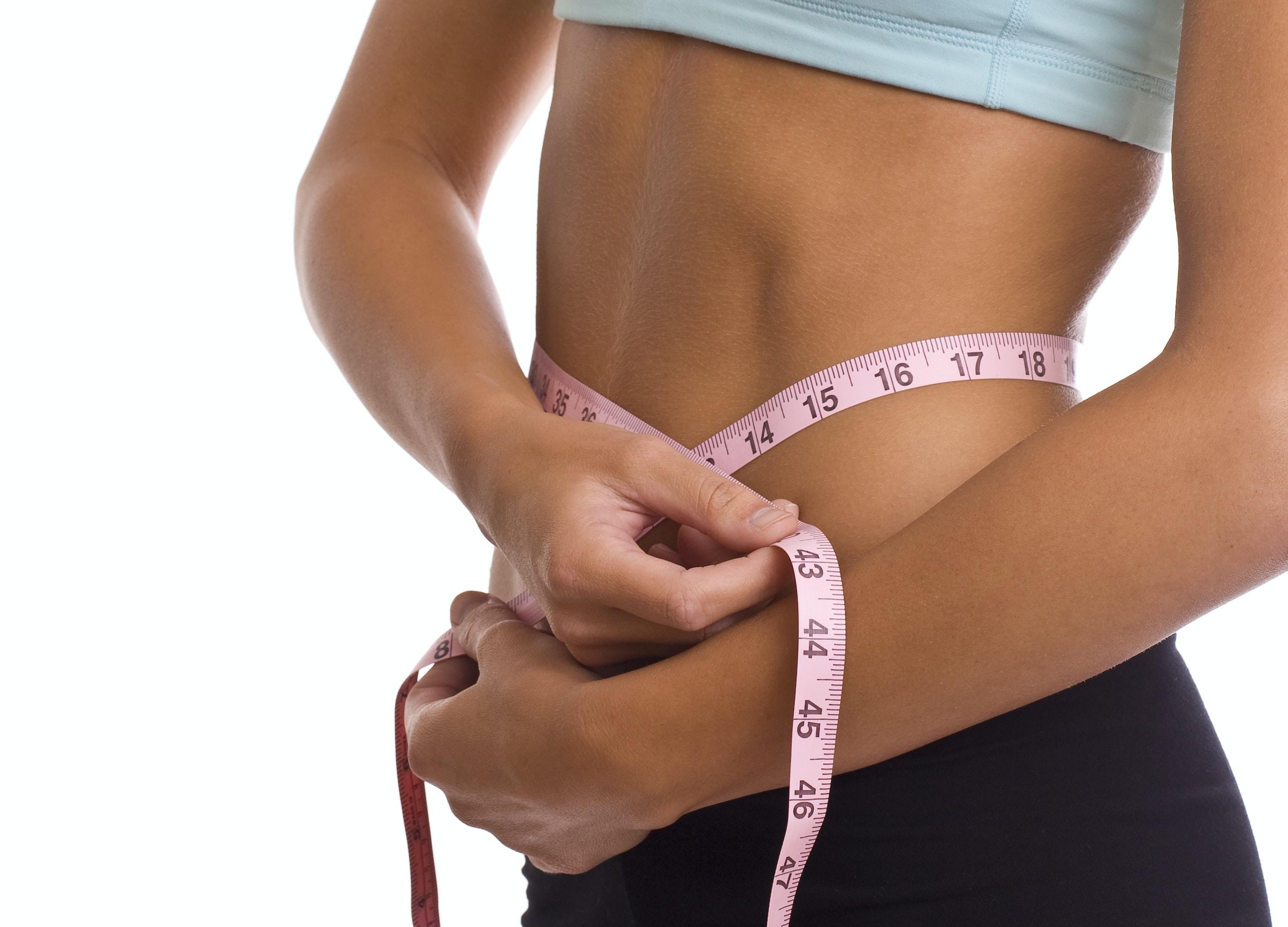 ayuno intermitente, woman using body tape measure while measuring her waist