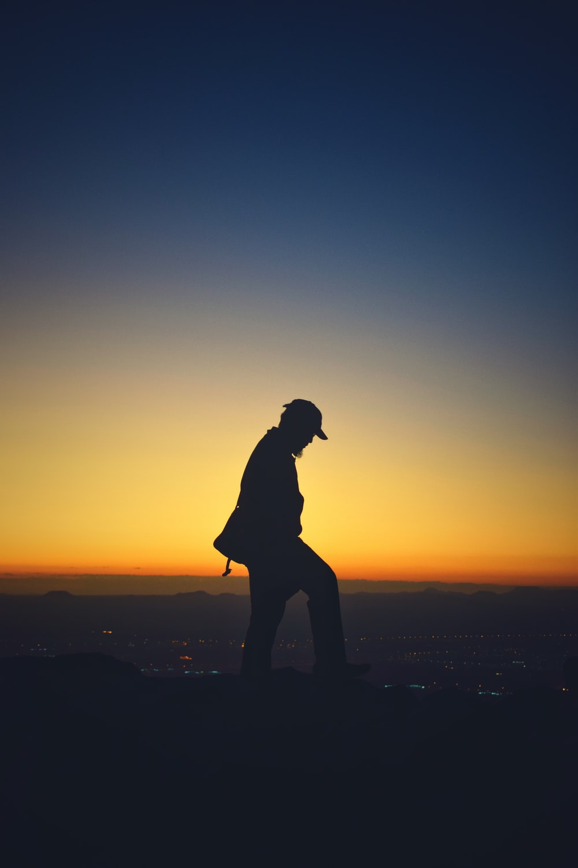 silhouette of man wearing cap