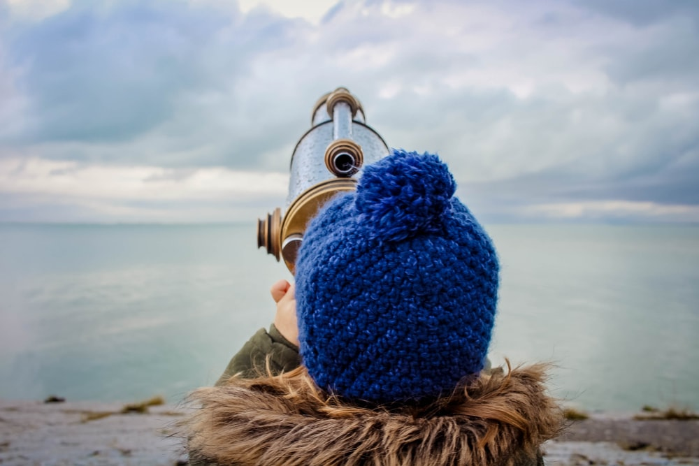 toddle in front of gold and silver telescope on beach