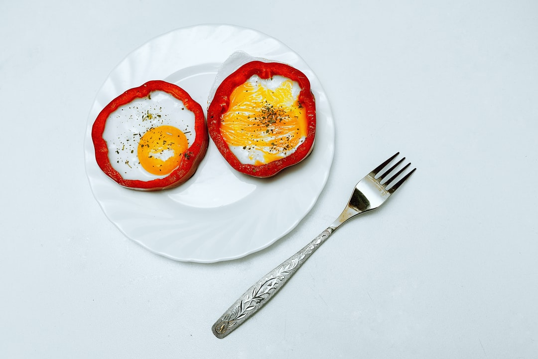 Bright and juicy picture with orange eggs and red sweet pepper. The eggs are on a plate, next to the plate there is a fork. Beautiful frame with appetizing food.