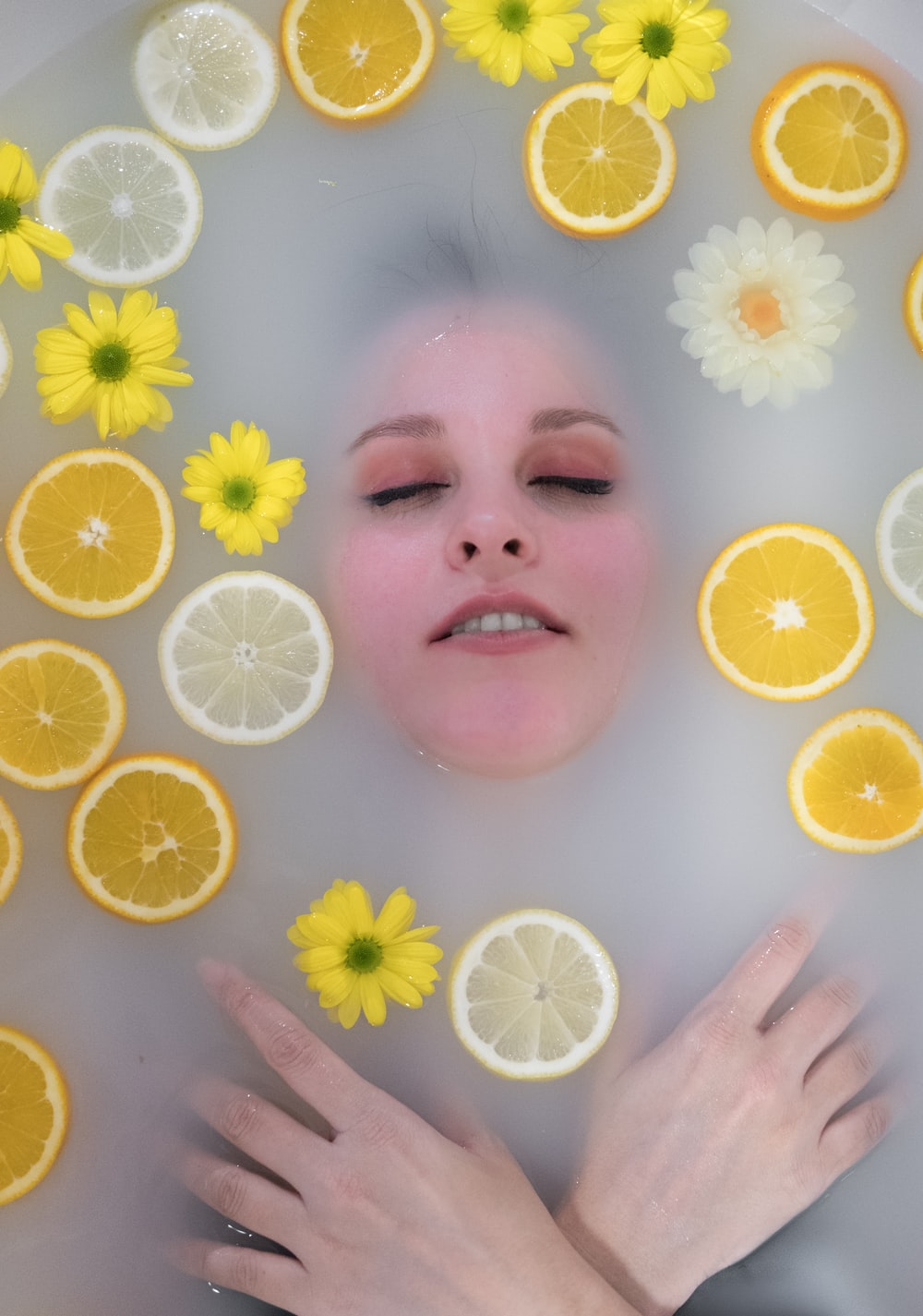 flat-lay photography of woman dipped in water surrounded by yellow lemons and flowers