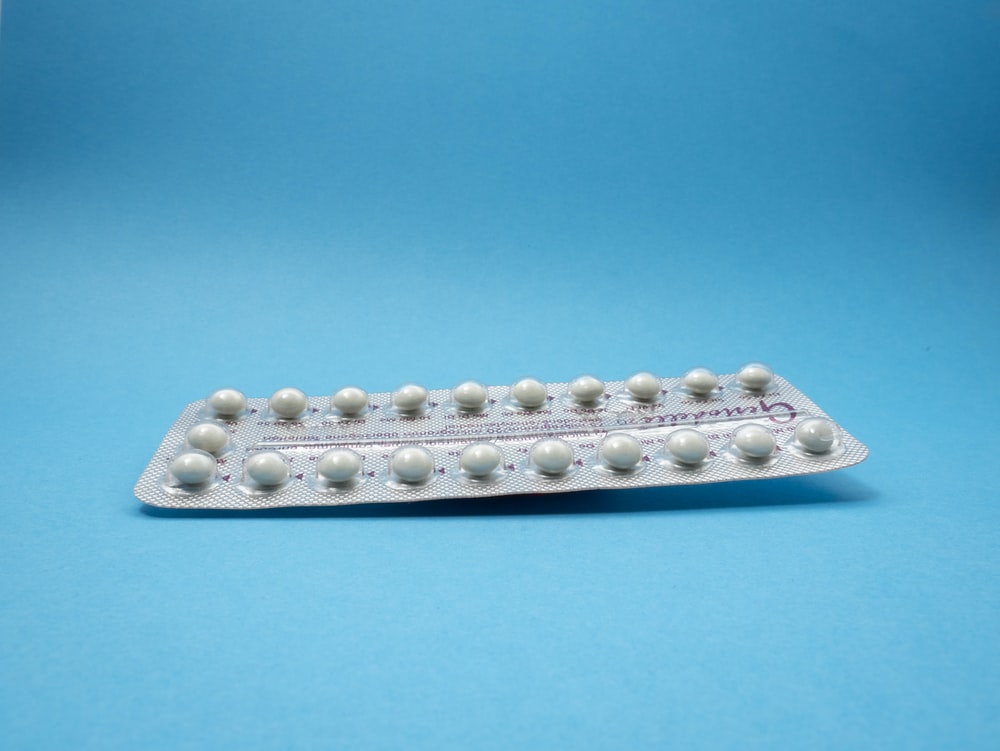 oral contraceptive pill on blue panel