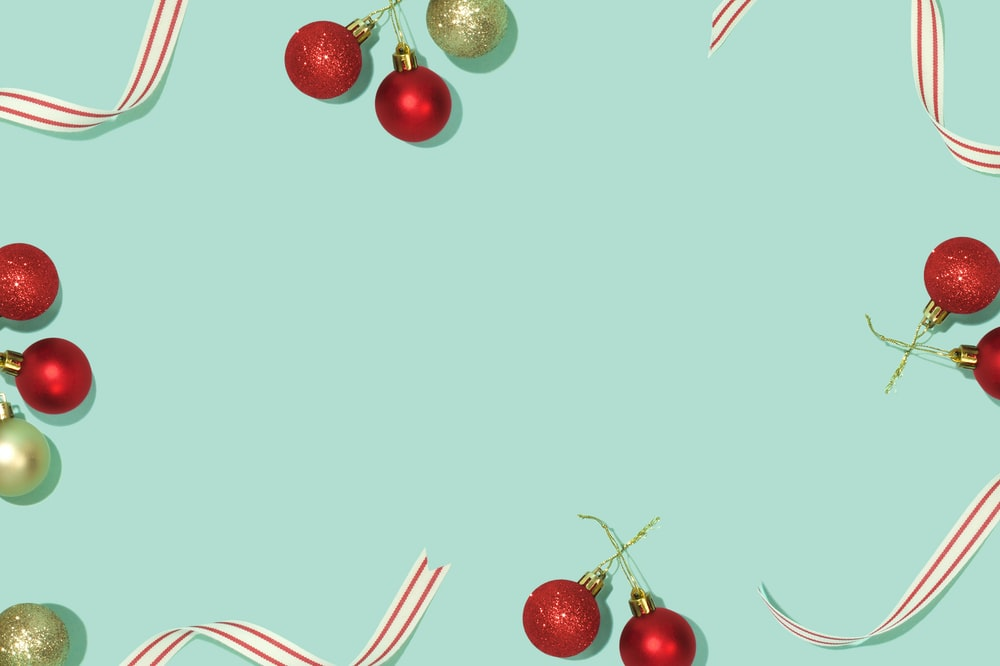flat lay photography of red and gold Christmas baubles on teal background
