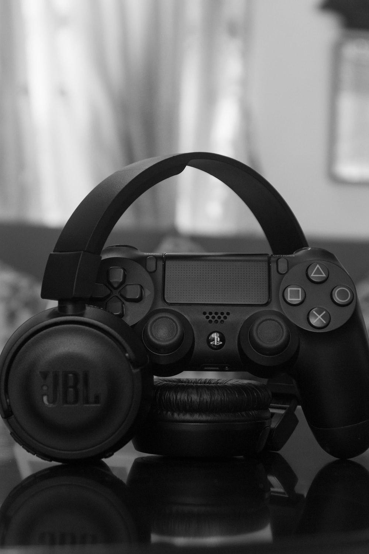 Sony PS DualShock 4 beside JBL wireless headphones