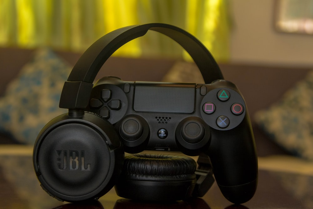 black Sony PS4 controller and JBL headphones