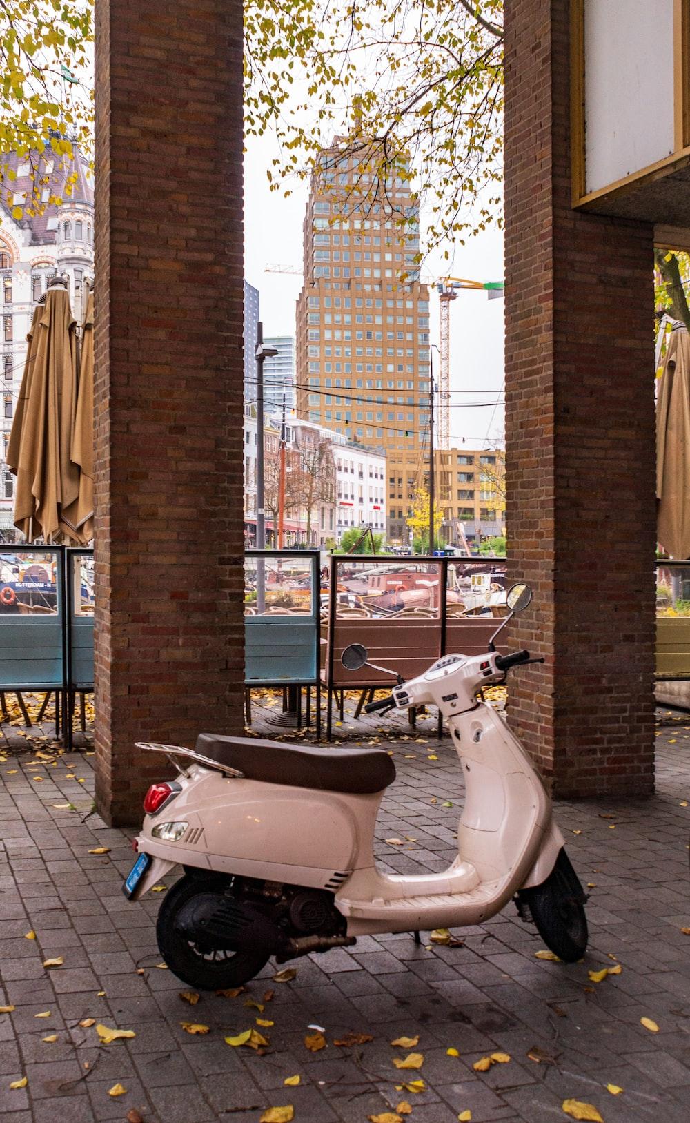white motor scooter parked near pillars