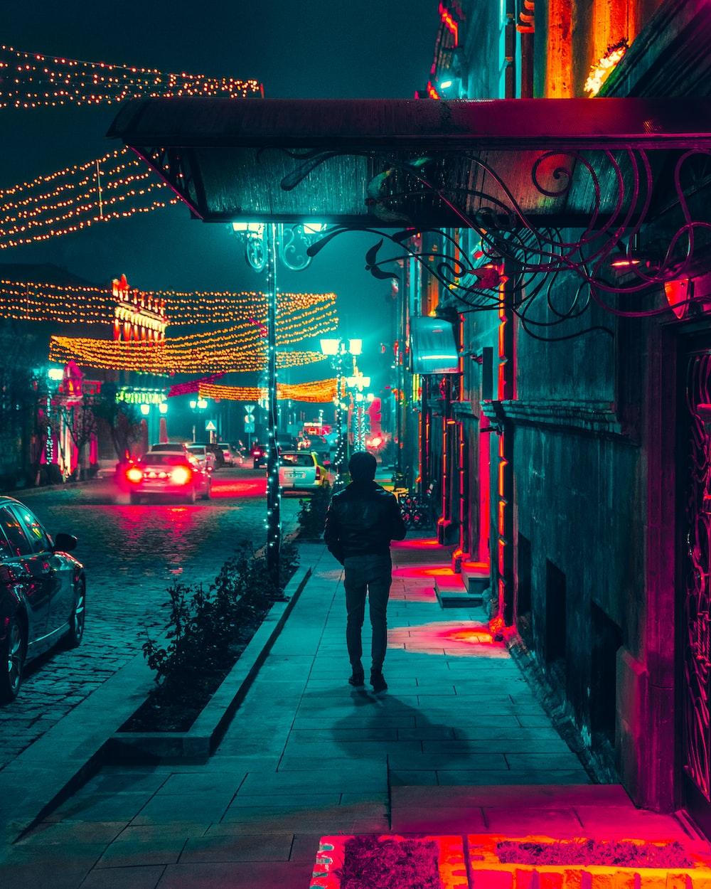 man walking along a sidewalk during nighttime