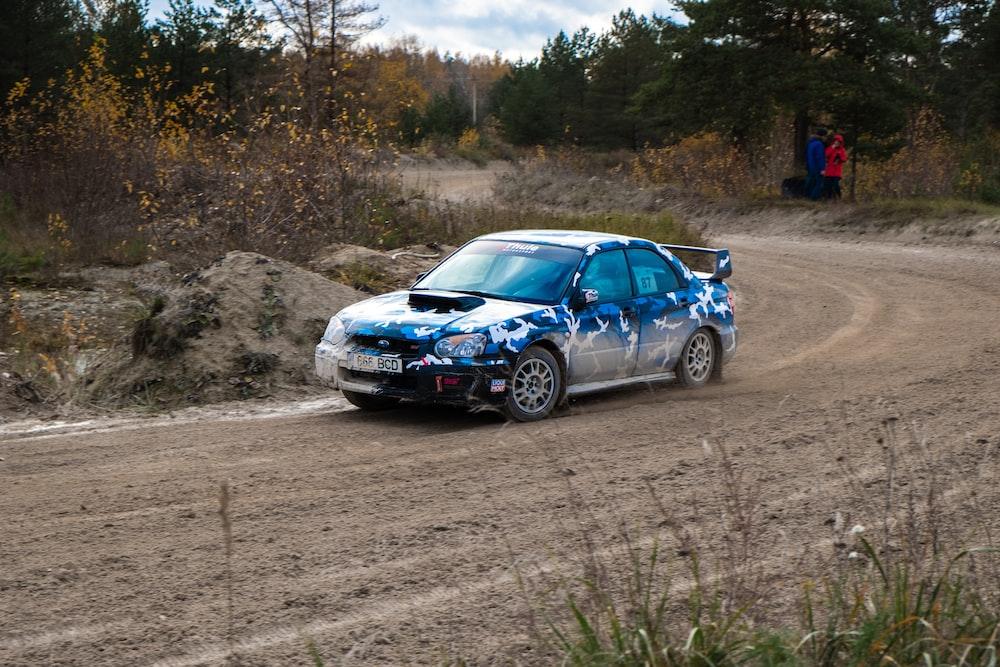 blue sedan passing by a rough road